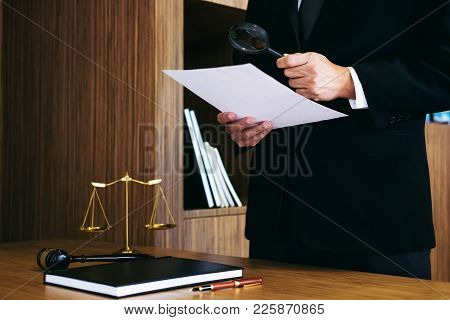 Male Lawyer Reading Legal Contract Agreement And Examining Documents With Magnifying Glass In Courtr