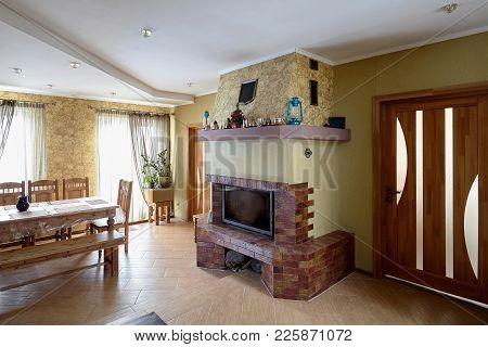 Fireplace And Table In Livingroom With Cups, Lamps And Christmas Tree On Mantelpiece