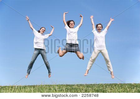 Three Girlfriends Jump Having Waved Hands