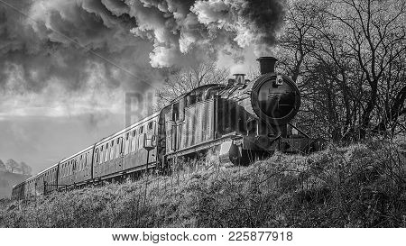 A Black And White Mono Close Up Photograph Of A Steam Train Locomotive And Carriages Smoking And Fro