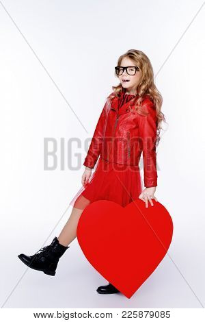 Full length portrait of a pretty pre-teen girl holding big red heart. Isolated over white. First love. Valentine's Day.