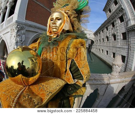 Venice, Italy - February 5, 2018: Person In Costume With Golden Mask Near The Famous Bridge Called P