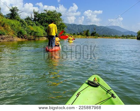 People Going Down Nam Song River In Kayaks Near Vang Vieng, Vientiane Province, Laos. Kayaking Is A