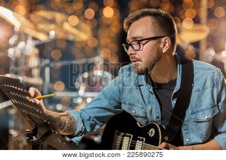 people, composition and entertainment concept - man with guitar writing lyrics or notes to music book at studio over holidays lights background