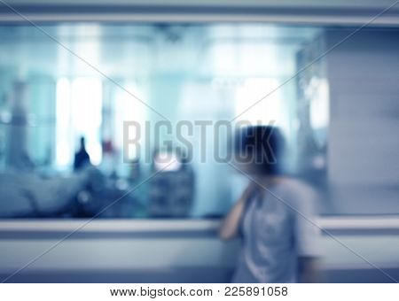 Female Nurse Looking Through The Observation Window Of Hospital Ward, Unfocused Background.