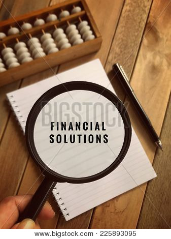 Financial Solutions Concept. Financial Solutions Words On Magnifier Glass And Background Of A White