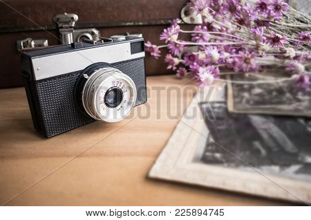 Close Up Of Old Camera Lens Over Blurred Background Of Old Leather Suitcase,  Retro Shoots And Purpl
