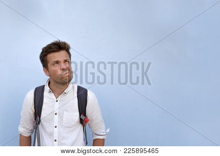 Caucasian Mature Man In White Shirt Looking Up. He Is Not Sure About Something. Blue Copyspace
