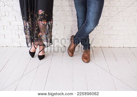 Two Pairs Of Male And Female Legs In Shoes Are Crossed. Couple Standing In Front Of The White Wall C
