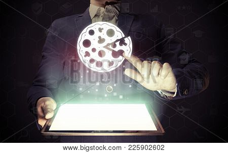 Image Of A Man With A Tablet Pc In His Hands. He Presses On The Pizza Icon. Search And Online Order