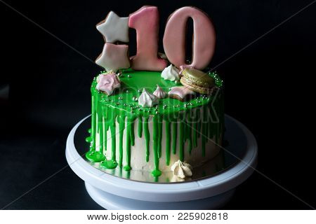 Cake With Green Glaze And Number Ten, Stars, Meringue, Macaroons, On A White Stand On A Black Backgr