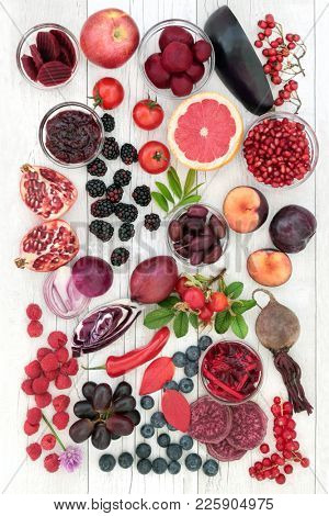 Health food concept with fruit and vegetables high in anthocyanins, antioxidants and vitamins on   rustic wood background. Red, purple and blue food denoting presence of anthocyanins.