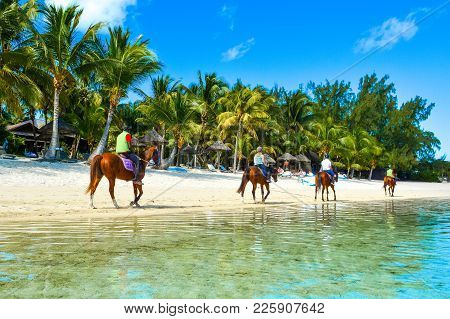Le Morne, Mauritius - 17 July 2017: Tourists On Horses Walking Along The Coast Of The Indian Ocean N