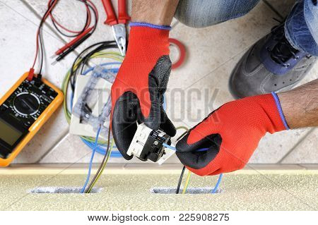 Electrician Technician At Work Sticks The Cable Between The Clamps Of A Socket In A Residential Elec