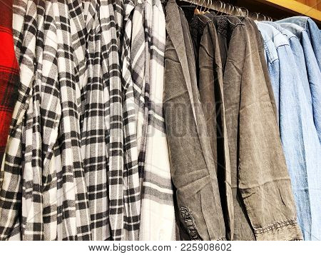 Modern Clothes In A Shop On A Hanger. Shirts And Sweaters Of Different Colors And Denim For Youth. C