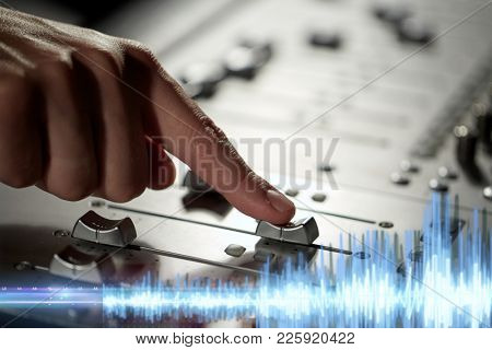 music, technology and equipment concept - male hand moving switch on mixing console in sound recording studio
