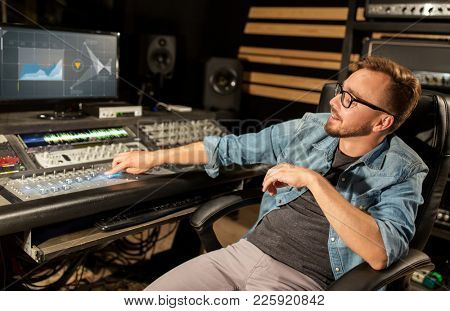 music, technology, people and equipment concept - man at mixing console with computer monitors in sound recording studio