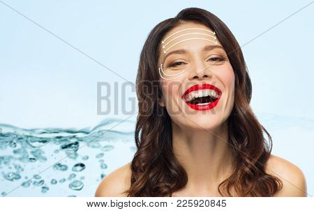 beauty and anti-age concept - happy laughing young woman with face lifting arrows over blue background with water splash