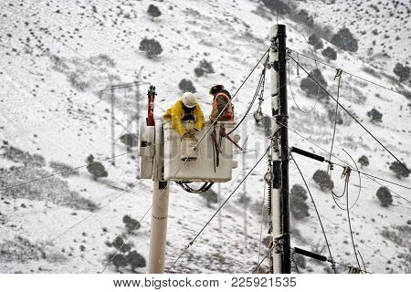Electrical Workers Working On A Power Line In A Snow Storm