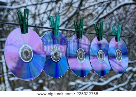 A Row Of Compact Discs Hang On A Wire On Clothespins On The Street