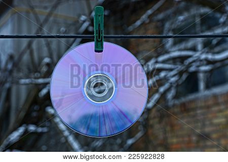 Round Compact Disc Hanging On Wire On Clothespin