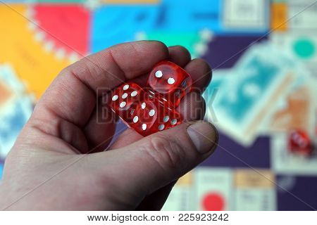 Red Game Cubes In The Palm Of A Hand Over A Board Game