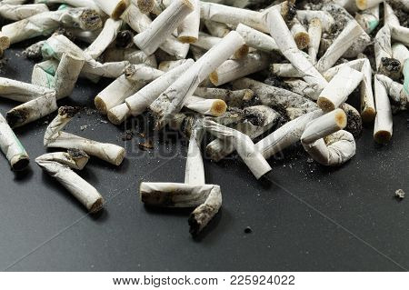 Heap Of White Cigarette Butts, Slim Type And Scattered Ash. Dark Background