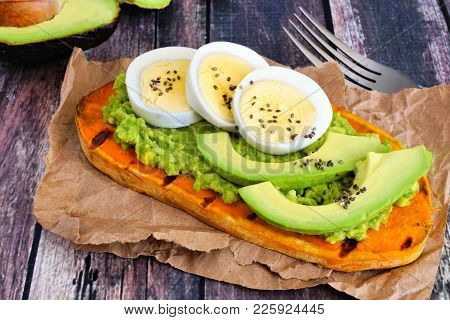 Sweet Potato Toast With Avocado, Eggs And Chia Seeds. Table Scene With A Wooden Background.