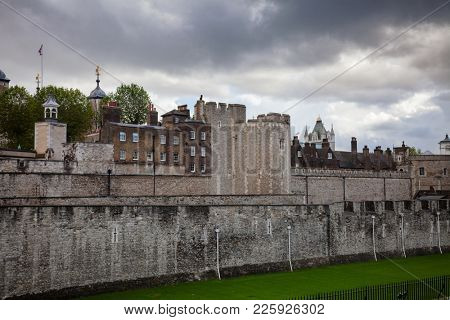 The outer curtain wall and dry moat of Tower of London - historic castle and popular tourist attraction on the north bank of the River Thames in central London England UK