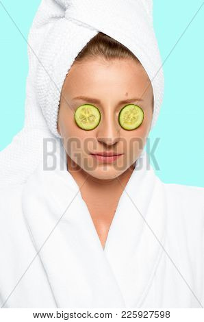 Beauty And Spa. Beautiful Woman With Cucumbers On Eyes And Towel On Her Head On Faded Pastel Backgro