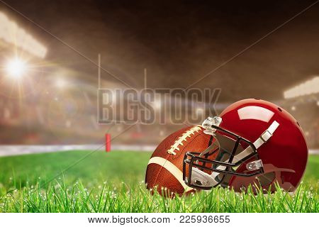 American Football Helmet And Ball On Field Grass In Brightly Lit Outdoor Stadium With Focus On Foreg