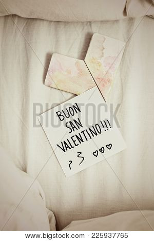 high angle view of a white paper note with the text buon san valentino, happy valentines day in italian written in it, and an origami heart on an undone bed, with a dramatic effect