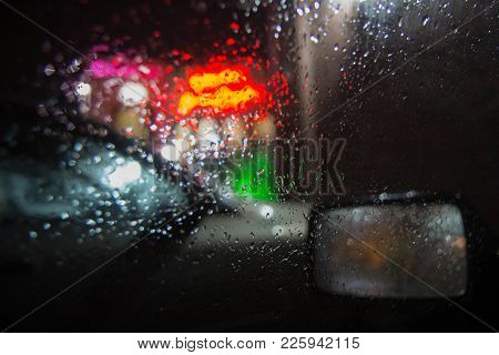 Rain On The City Street Through A Car Windshield. Rain Drops On Window, Rainy Weather, Night. Inside
