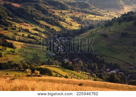 A Beautiful Summer Rural Landscape With Houses, Sunny Hills And  Many Small Hay Stacks. Carpathian R