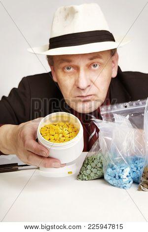 Older Dealer Of Mdma Drugs Showing Lot Of Pills