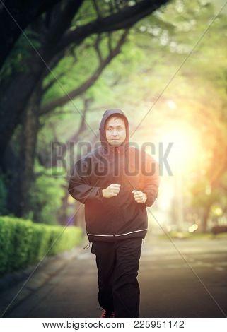 Sport Healthy Man Wearing Hood Jacket Running In Green Park
