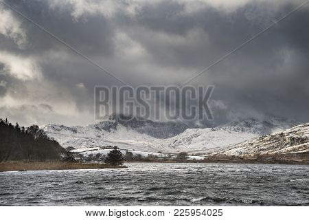 Beautiful Winter Landscape Image Of Llynnau Mymbyr In Snowdonia National Park With Snow Capped Mount