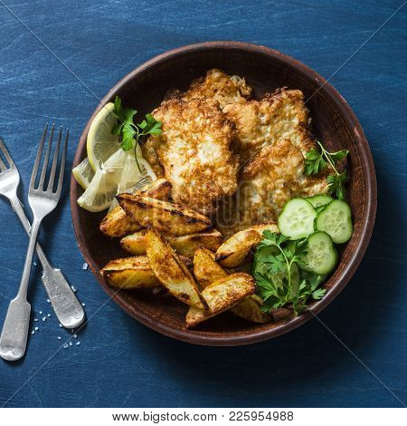 Fried Fish And Garlic Baked Potatoes On A Blue Background, Top View. Fish And Chips