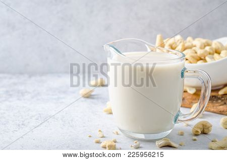 Cashew Milk In A Milk Pitcher With Cashew Nuts On A Light Stone Background. Front View, Horizontal I