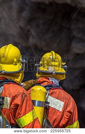 Two Firefighters Standby For Water Sprey Surround With Black Smoke And Copy Space