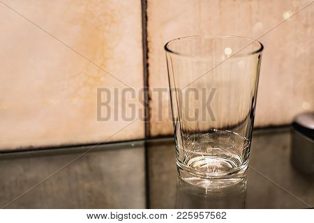 A Litte Bit Of Water In A Glass Standing On A Glass Shelf In Tiles Background. Close Up.