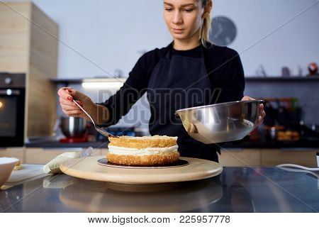 A Confectioner Woman Makes  Cake In The Kitchen In A Pastry Shop.