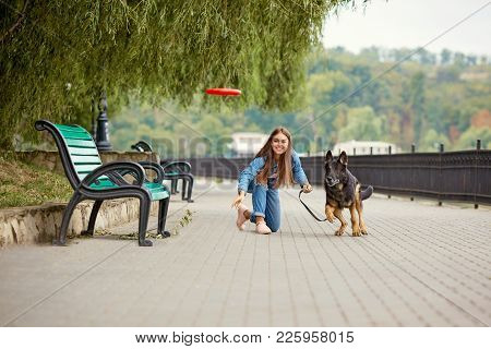 A Young Girl Is Walking With A German Shepherd Dog In The Park.