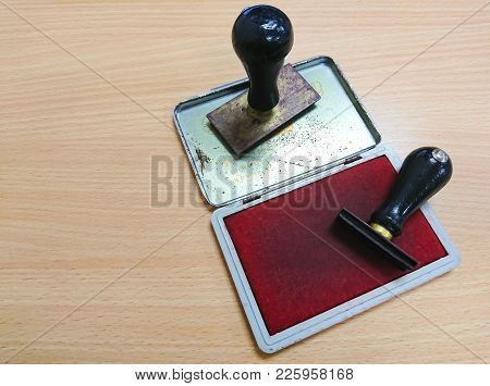 Two Rubber Stamps Lying On The Wooden Table
