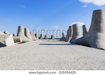Breakwaters Against The Blue Sky Of The Black Sea Of Bulgaria