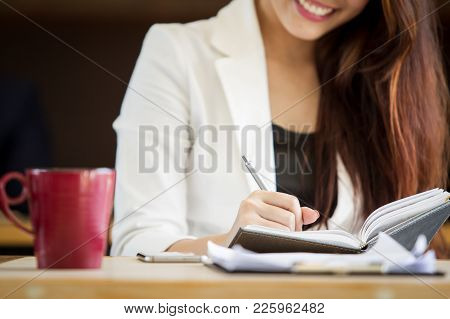 Business Women Writing Something On Her Notebook Close Up.