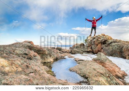 mature backpacker enjoying reaching a on a mountain top - Horsetooth Rock trail above Fort Collins in northern Colorado