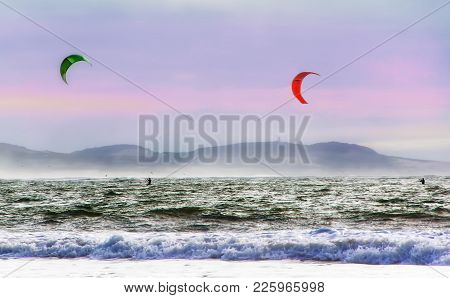 Kite Surfers Glide On The Waves Of The Atlantic Ocean. Extreme Sport Concept. Active Leisure Landsca