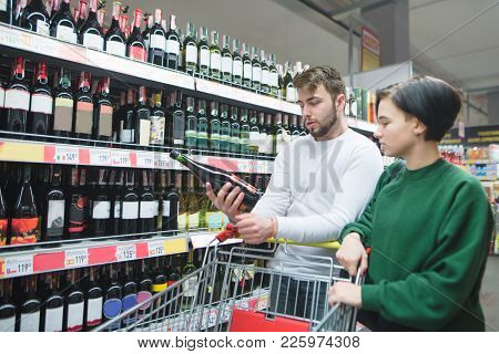 A Young Couple Looking At A Bottle Of Wine At A Supermarket. Young Couple In The Alcohol Department