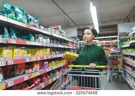 Portrait Of A Buyer Girl With Packaging In The Middle Of A Supermarket. A Beautiful And Positive Gir